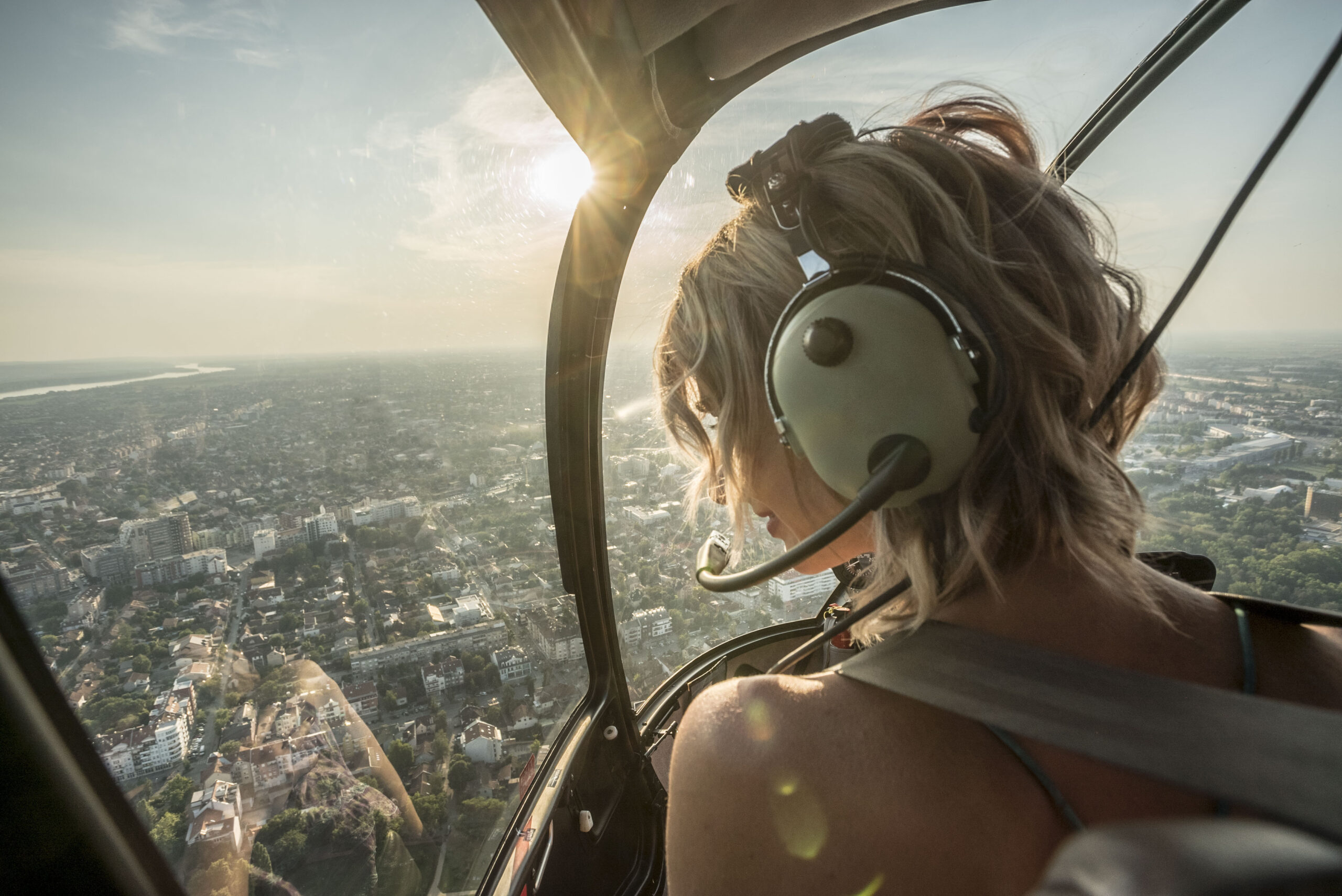 Portrait of beautiful blonde women enjoying helicopter flight. She is amazed by cityscape and wearing pilot headphones.